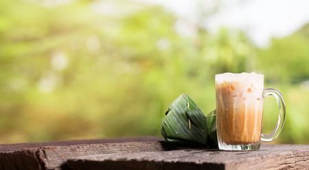 Thai iced tea milk signature local street beverage serve with dessert on wooden table Imagens