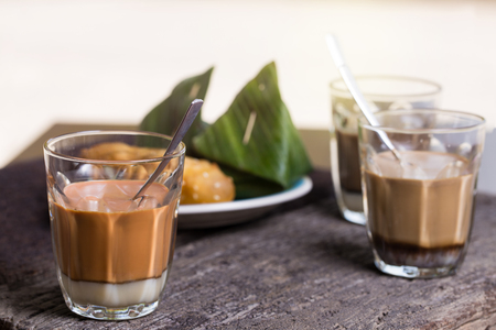 hot drink thai milk tea, black coffee, cocoa signature local street beverage serve with dessert on wooden table