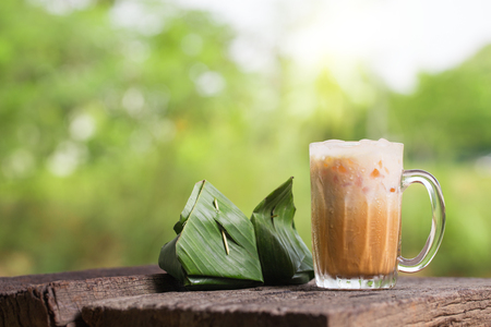 Thai iced tea milk signature local street beverage serve with dessert on wooden table Imagens