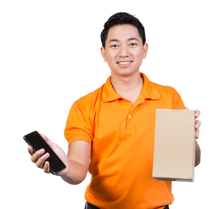 young man delivery box package smile face hand hold mobile phone and cardboard isolated on white backgound Imagens