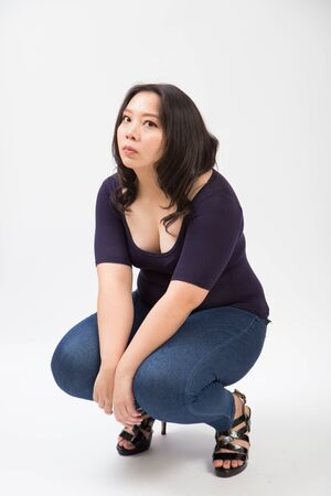 woman plus size sitting on shoe pose in studio white background