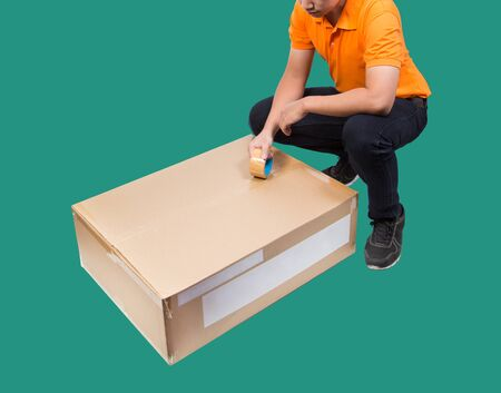 man packing package box with tape isolated on green background