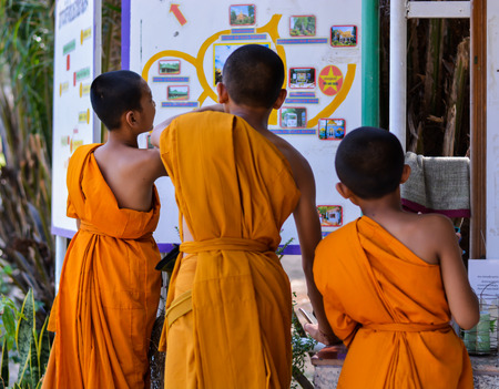 ROI Et THAILAND : Three unidentified young monks are looking at the map of Maha Chedi Chai Mongkol temple where is one of the largest chedis pagoda in Thailand. It is located on the grounds of the Wat Pha Namthip Thep Prasit Vararam a temple complex in Ro