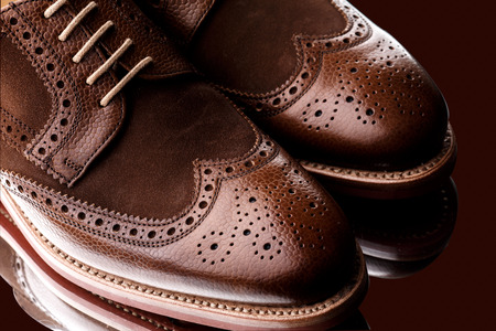 brogues: Unworn, laced pair of two tone men brogues  derbys  with elegant toe shape  The upper is stunning combination of brown calf with brown suede  Isolated on dark brown background with mirror reflection  Stock Photo