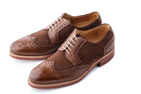Unworn, laced pair of handcrafted shiny, two tone men brogues  also known as derbys, gibsons or wingtips  on durable welted red brick rubber sole  The upper is stunning combination of brown calf with brown suede  Isolated on white background with soft dif