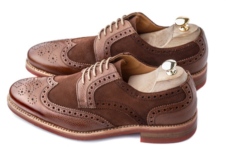wingtips: Unworn, laced pair of handcrafted shiny, two tone men brogues (also known as derbys, gibsons or wingtips) with shoe trees inserted on durable welted red brick rubber sole. The upper is stunning combination of brown calf with brown suede. Isolated on white