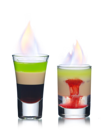 Two burningcocktails in shot glasses