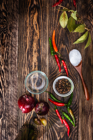 piper: Spices on wooden table. Top view of kitchen table with pepper,piper, onion and bay leaves.