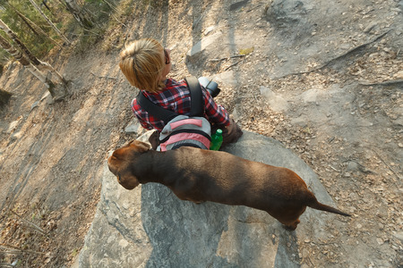 ascend: Female tourist sitting on the boulder with her dog while resting before hard ascend. the view from above.