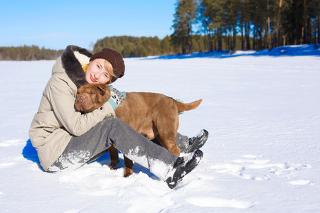 pinery: Woman hugging her shar pei while sitting on the snowy field near a pinery on a sunny day