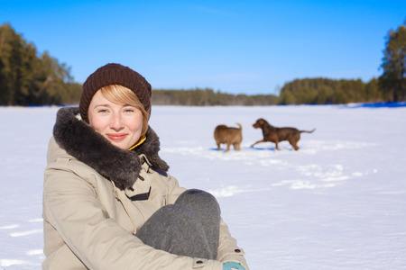 pinery: Woman sitting on a snowy field near a pinery on a sunny day while her dogs playing and frolicking behind Stock Photo