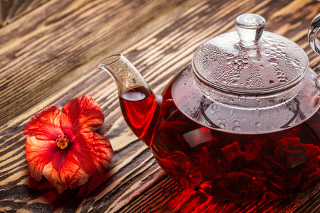 Hibiscus tea in transparent teapot on wooden table