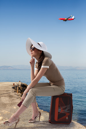 pierce: Traveling stylish woman sitting on her luggage on the pierce near the sea while holding her passport and dreaming. Travel,vacation,tourism concept. Stock Photo