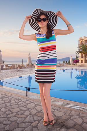 complement: Stylish woman wearing sunglasses, striped dress with complement hat posing against hotels waterpool at a dawn. Vacation, travel concept.