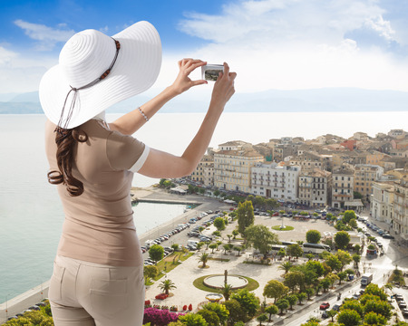 kerkyra: Female tourist taking a picture of the Kerkyra (Corfu) downtown from new fortress on her smartphone on a sunny day. Vacation, travel, tourism concept