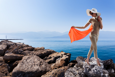 pierce: Stylish woman standing on the pierce against gorgeous seascape while holding her red streaming scarf. Vacation, travel concept