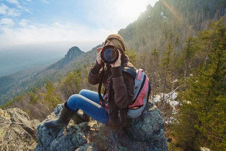 Adventurous female photographer sitting on the rock while photographing mountains facing the off scene viewer against the setting sun. Wide angle perspective. Tourism, adventure, hiking concept. Standard-Bild