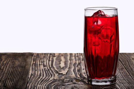 Iced hibiscus tea also known as Flor de Jamaica on wooden table against plain background