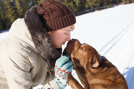 sharpei: Woman playing with her shar pei on a winter sunny day Stock Photo