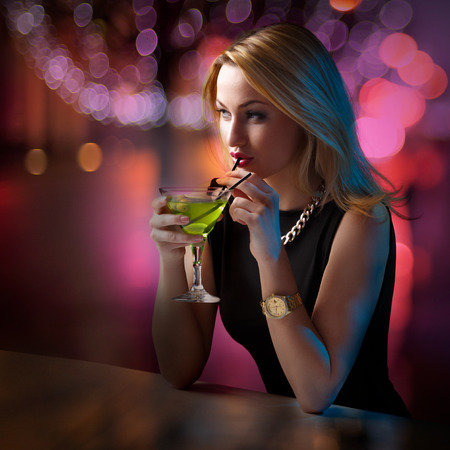 looking around: Young attractive woman looking around leaning on the bar counter while sipping her cocktail Stock Photo