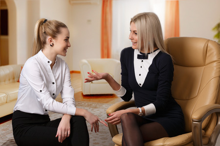 Two formal dressed elegant women talking each other in relaxed atmosphere