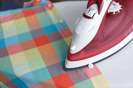 ironing board: Close up of iron on ironing board near the plaid shirt. Focus on steam control knob