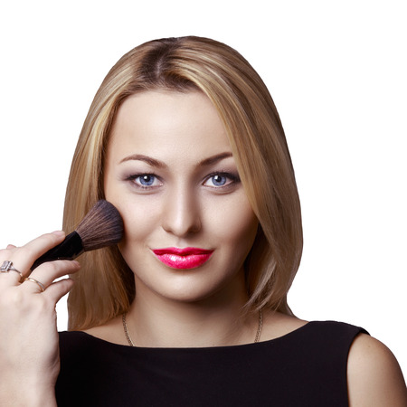 Attractive young adult women looking straight while presses makeup brush to her cheek Stock Photo