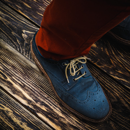 Close up of mens brogues (also known as derbies,gibsons or wingtips) made from blue oiled suede.