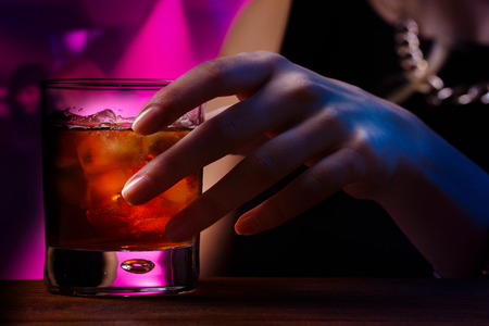 Woman's hand holding old fashioned glass with cold cocktail against blurred night club background