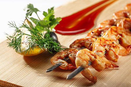 Grilled shrimps on a elegant skewers decorated with greens and sauce