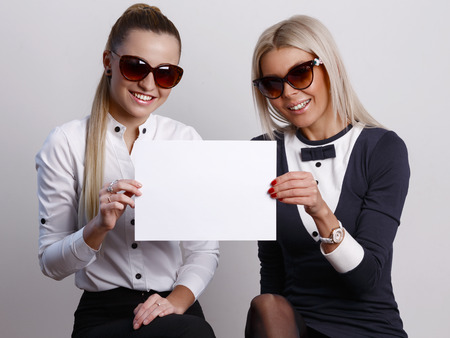 looking ahead: Two girlfriends in sunglasses looking ahead while holding a blank sheet of paper together