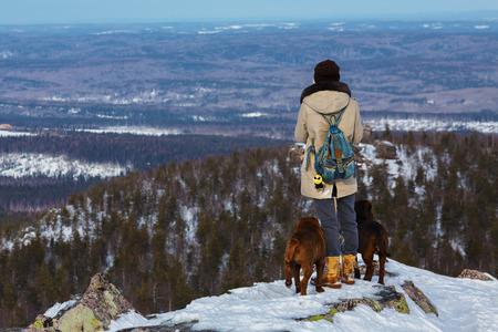 adventurous: Adventurous woman standing on a snowy rocks ledge near her dogs while looks afar Stock Photo