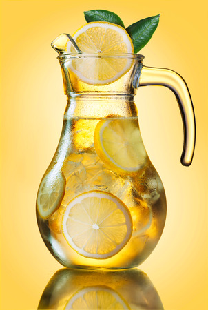 misted: Misted lemonade pitcher with lemon slices and ice cubes decorated with leaves on yellow.