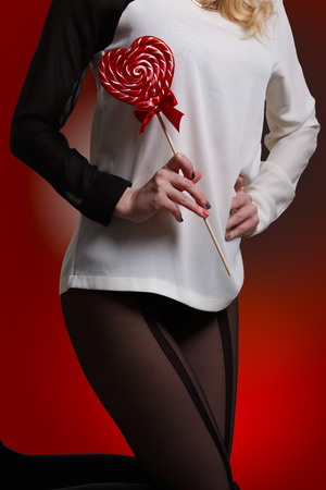 kneeling: Woman wearing tights holding heart shaped lollipop while kneeling