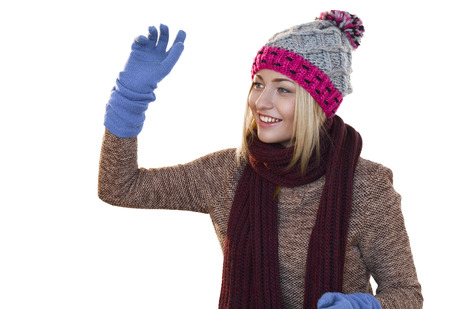 imaginary: Attractive woman wearing winter clothes smiling while throwing imaginary snowball (not shown)