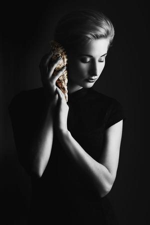 Fine art Monochrom Porträt der schönen Frau, die dezent Farbe akzentuierten Muschel beim Hören imaginären Klängen des Ozeans. Niedrige Schlüsselbild Standard-Bild