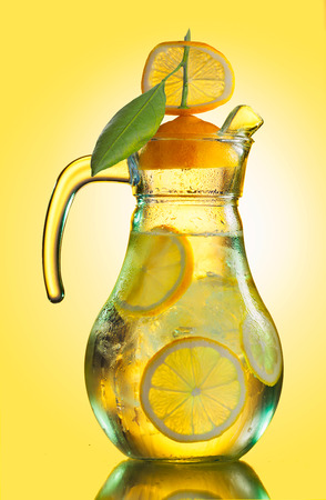 misted: Misted lemonade pitcher with lemon slices and ice cubes decorated with quarter lemon cap  on yellow Stock Photo