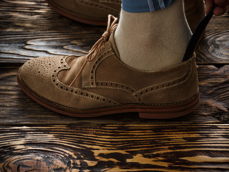 wingtips: Putting on shoes. Close up of male foot in suede brogue