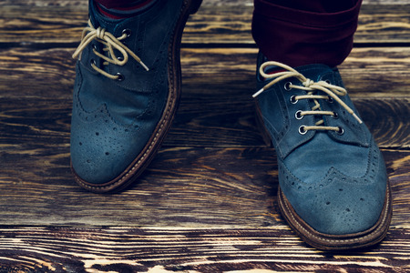 oiled: Close up of mens brogues (also known as derbies,gibsons or wingtips) made from blue oiled suede. Vintage styled