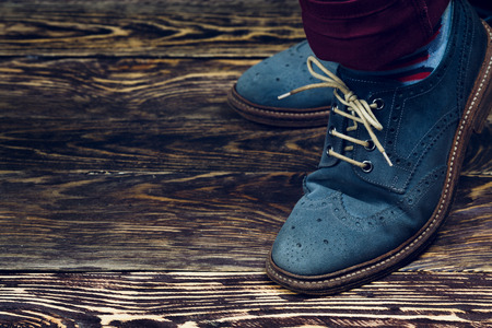 Close up of men's brogues (also known as derbies,gibsons or wingtips) made from blue oiled suede. Vintage styled