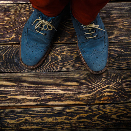 Close up of mens brogues (also known as derbies,gibsons or wingtips) made from blue oiled suede. Top view