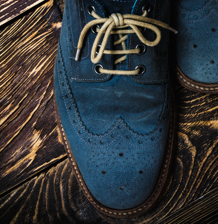 Close up of mens brogues made from blue oiled suede.