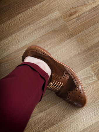 preppy: Sockless male leg in two tone suede brogue, Stylish dressed man wearing cushioned pants and wingtips Stock Photo