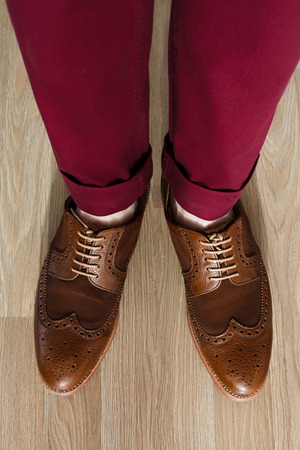 Sockless male legs in two tone suede brogues, Stylish dressed man wearing cushioned pants and wingtips