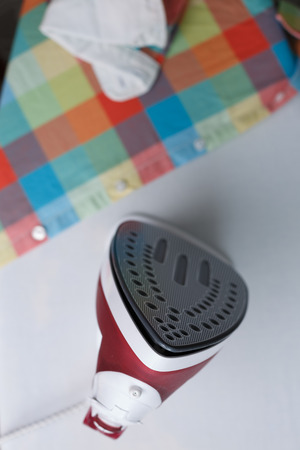 ironing board: Top view of iron on ironing board near the plaid shirt. Focus on irons tip