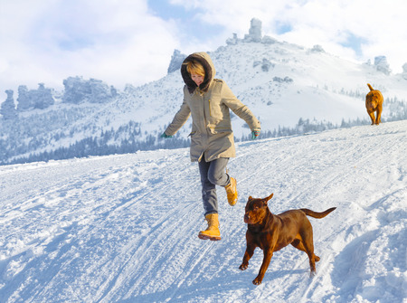 anorak: Woman running and jumping with dogs in the snow field against distant mountains on a sunny day