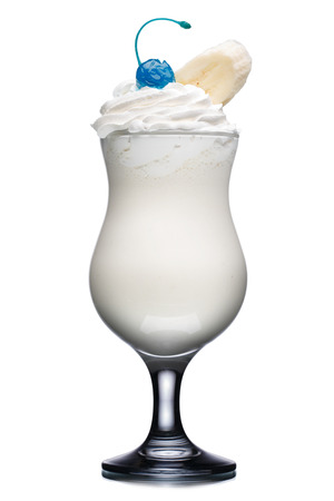 banana slice: Milk cocktail in hurricane glass decorated with blue cherry and banana slice. Fresh, clean look.