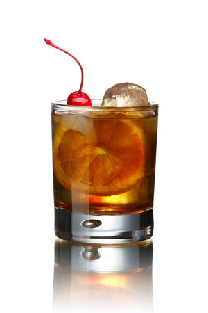 Old fashioned alcoholic cocktail decorated with Maraschino cherry. Before dinner IBA official cocktail.