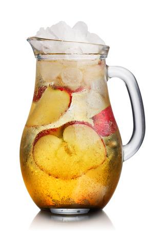vaso de jugo: Jarra de cristal de spritzer casera (apfleschorle) servido con hielo y rodajas de manzanas trituradas. Jarra llena de jugo de manzana con gas brillante y fría sin alcohol.