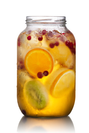 fres: Glass jar of homemade spritzer (schorle) with carbonated apple juice served with frozen fruit wheels, ice cubes and wild cranberry Stock Photo